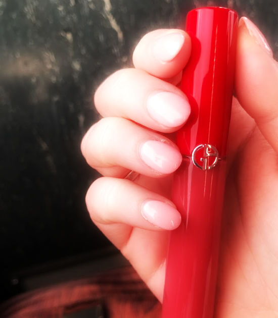 Manicured hand holds liquid lipstick.